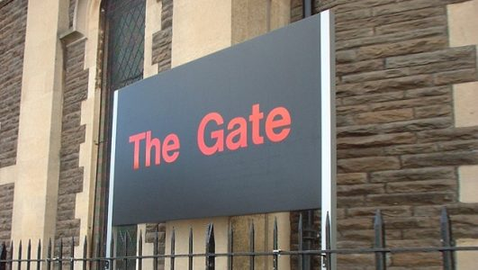 The Gate Bristol Post Mounted Sign elevated above Railings